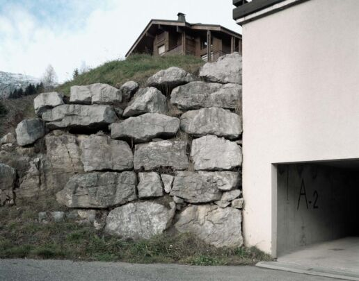 Stonewall beside car park entrance. Typical chalet on the hill.