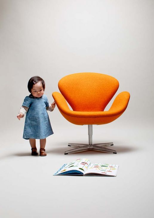 a toddler standing near swan chair