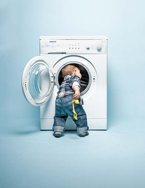 toddler at a washing machine