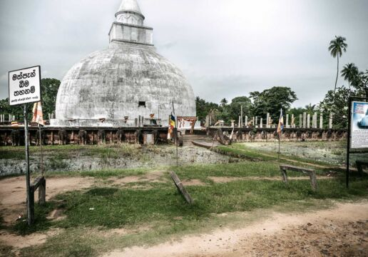 white stupa behind tarn some signs standing around. Tissamaharama.